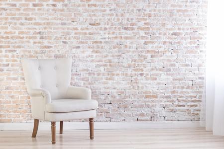 Photo pour White Armchair On Brick Wall Background Near Window - image libre de droit