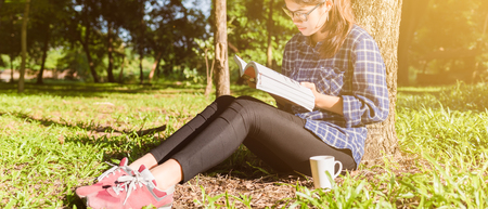 The girl sitting on a green grass with cup of coffee and reads the book, young woman  with coffee sitting on the grass and reading a book in the park banner panoramic crop for copy space.