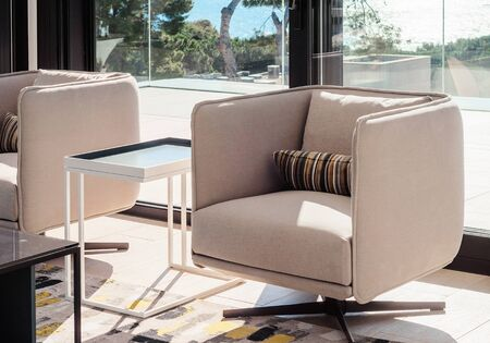 Photo pour Modern living room interior with swivel chairs and coffee table, opposite window overlooking the sea.  Details of the decor in a luxury home.  Decor background.  - image libre de droit