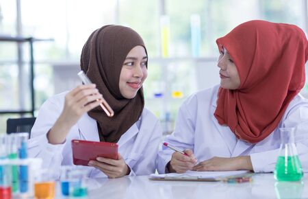 Photo pour Two female muslim scientists wear white coat  with reagent during experiment in chemical lab. - image libre de droit