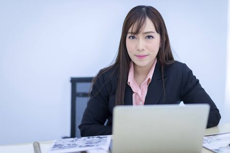 Photo pour Beautiful Asian businessman wearing a black suit sitting in the office, smiling confidently and looking at the camera. Asian business women, business owners, and office staff. Concept - image libre de droit