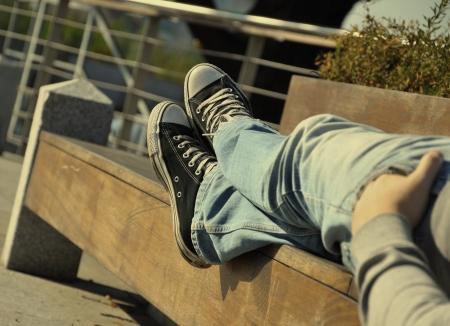 Legs of a boy lying on a bench