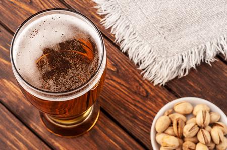 Foto de Composition with glass of beer on wooden background. Closeup. - Imagen libre de derechos