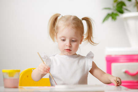 Photo pour Pretty Little Girl Draws Watercolors While At Home In Her Room. The Child is Engaged In Creativity. Little Artist. - image libre de droit