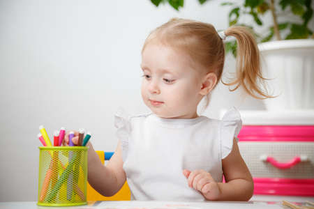 Photo pour Little Baby Girl Painting At Table In Home Or Kindergarten Preschool. Cute Adorable Small Child With Two Pony Tails Drawing Indoor.Box With Multicolored Marker Pens. - image libre de droit