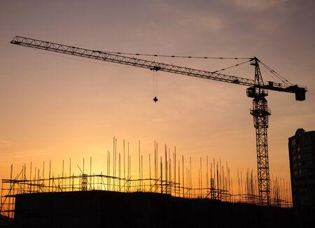 Foto de Silhouette of a crane in a construction site at sunset background - Imagen libre de derechos