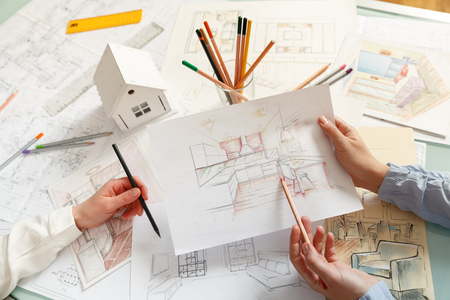 Photo pour Interior designers working on color hand drawings of a kitchen interior at work place. Photo of young designers work concept - image libre de droit