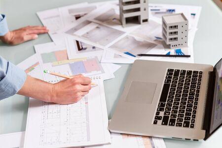 Photo pour Interior designer working with an apartment plans in a studio, with blueprints and laptop on a table. Architectural desigh bureau working concept - image libre de droit