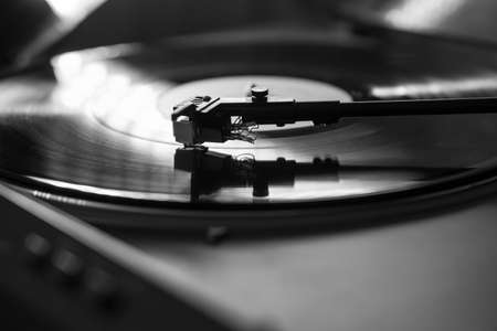 Photo pour Closeup view of a tonearm and turntable playing vinyl record. Entertainment and music trends, black and white image - image libre de droit