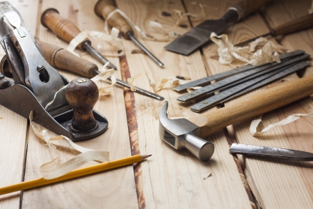 carpenter tools,hammer,meter,chisel and shavings over wood table