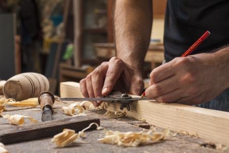 Photo pour hand of a carpenter taking measurement of a wooden plank - image libre de droit