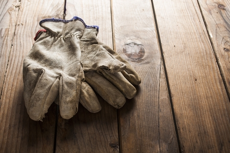 Old working gloves over wooden table, construction tools