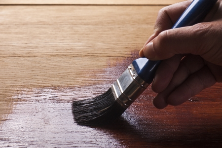 Photo for and holding a brush applying  varnish paint  on a wooden surface - Royalty Free Image