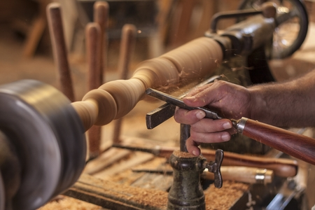 worker turning wood on a lathe