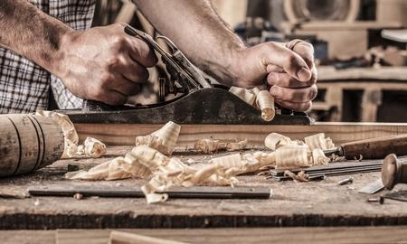 Photo pour carpenter working with plane on wooden background - image libre de droit
