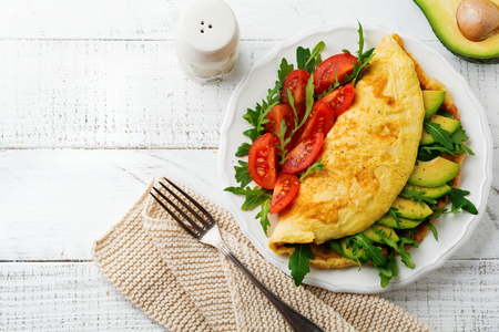 Omelette with avocado, tomatoes and arugula on white ceramic plate on light stone background. Healthy breakfast. Selective focus. Top view. Copy space.