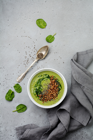 Useful smoothies from spinach with buckwheat flakes in ceramic bowls on gray concrete table background. Selective focus. Top view. Copy space.