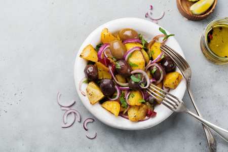 Warm potato salad with olives, pepper, parsley and red onion on old white ceramic plate on gray concrete background. Selective focus. Top view. Copy space.