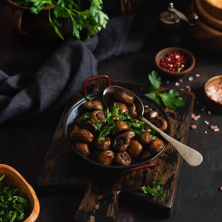 Foto de Mushrooms champignon fried in soy sauce, with pepper and steamed onions in an old metal bowl on an old vintage table. Selective focus. - Imagen libre de derechos