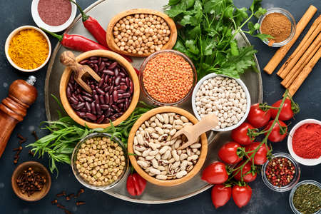 Photo for Legumes, lentils, chickpea, beans assortment, tasty appetizing ingredients spices grocery for cooking healthy kitchen on black table. Weight loss diet and fight against cholesterol concept. Top view. - Royalty Free Image
