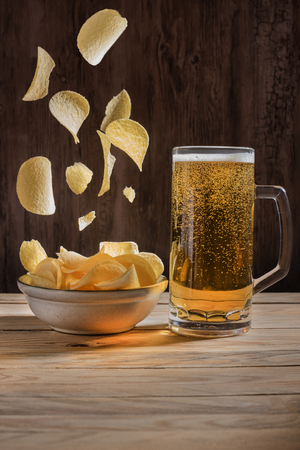 Beer and falling down crisps in golden light.