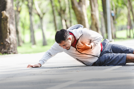Foto de Asian cardiac arrest running young man heart attack in park.Severe heartache - Imagen libre de derechos