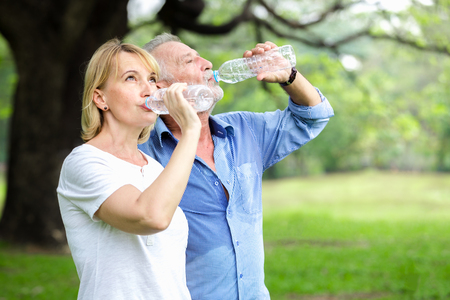 Foto de Portrait senior couple standing drinking water at the park - Imagen libre de derechos