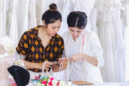 Foto de Asian designer working in wedding fashion store shop - Imagen libre de derechos