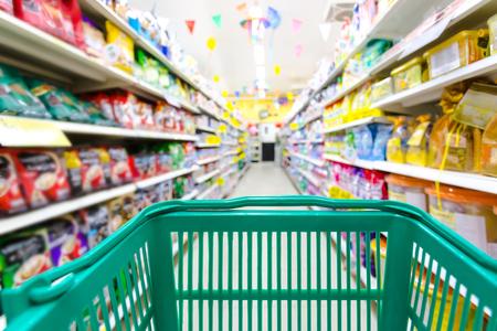Photo pour Closeup shopping basket green color with blurred suppermarket background - image libre de droit