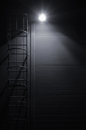 Fire emergency rescue access escape ladder stairway roof maintenance stairs at night bright shining lantern lamp light illumination glow shadows rustic textured industrial building wall panels texture pattern large detailed vertical closeup copy space bac