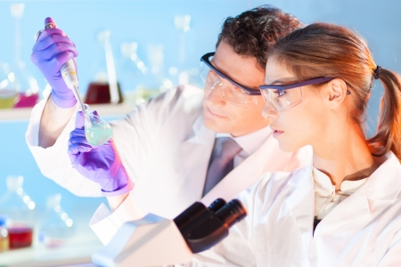 Chemical laboratory scene: attractive young student and her post doctoral supervisor scientist observing the green indikator solution color shift in glass flask.
