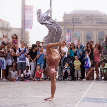MONTPELLIER - JULY 12: Street performer breakdancing in front of the random crowd on July 12, 2011 in  Montpellier, France; B-boying or breaking is a style of street dance that originated among African American and Puerto Rican youths in New York City dur