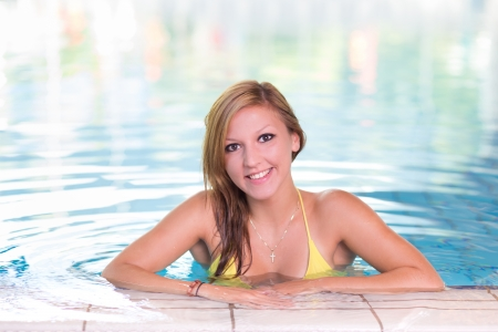 Young woman relaxing in the indoor swimming pool.