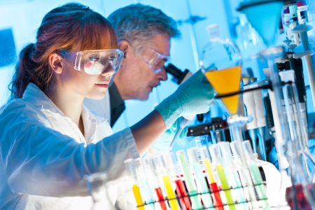 Attractive young female scientist and her senior male supervisor pipetting and microscoping in the life science research laboratory  biochemistry, genetics, forensics, microbiology