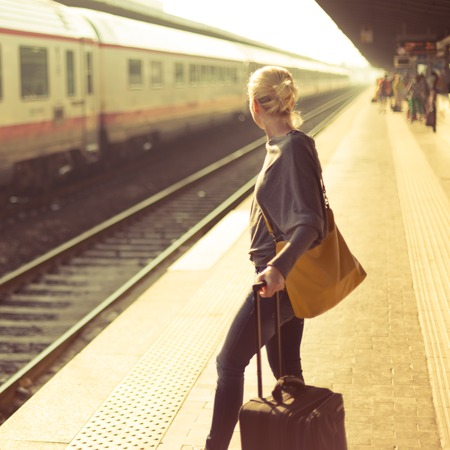 Blonde caucasian woman waiting at the railway station with a suitcase