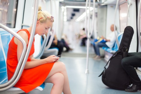 Beautiful blonde caucasian lady in red dress traveling by metro