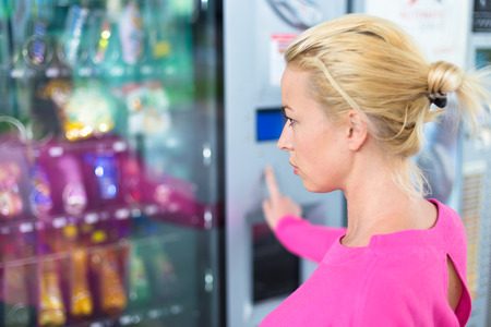 Caucasian woman wearing pink using a modern vending machine. Her right hand is placed on the dia pad.