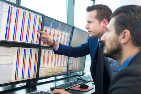 Stock traders looking at graphs, indexes and numbers on multiple computer screens