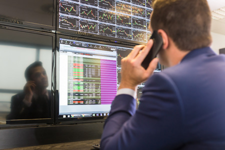 Businessman with cell phone trading stocks. Stock analyst looking at graphs, indexes and numbers on multiple computer screens. Stock trader evaluating economic data.