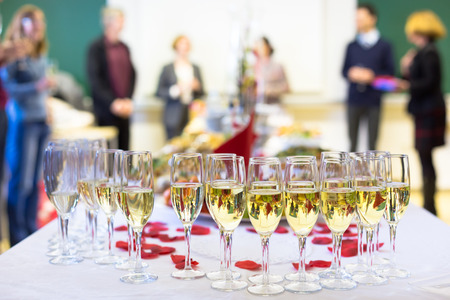 Photo pour Banquet event. Waiter pouring champagne into glass. Table with the wineglasses, snacks and cocktails. - image libre de droit