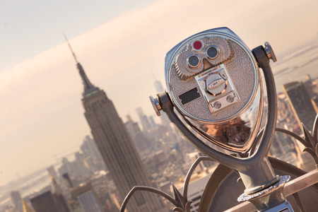 New York City, USA. Vintage tourist binoculars at Top of the Rock observation deck in front of Manhattan downtown skyline with Empire State Building and skyscrapers at sunset.