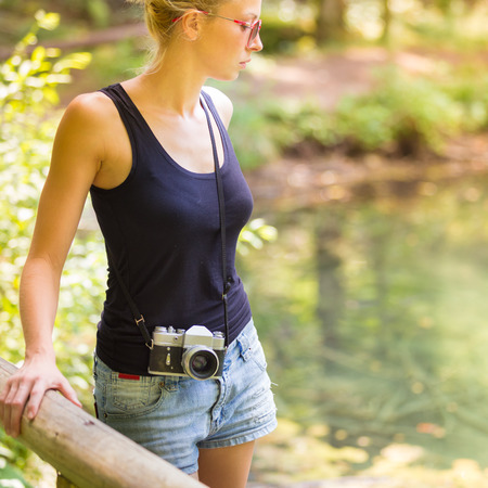 Beautiful blonde caucasian girl wearing jeans shorts an sporty black sleeveless t-shirt, outdoors in nature, carrying vintage camera over her shoulder. Healthy active lifestyle. Square composition.