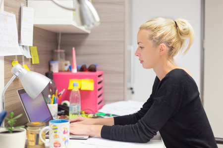 Business and entrepreneurship consept. Beautiful blonde business woman working on laptop in colorful modern creative working environment.