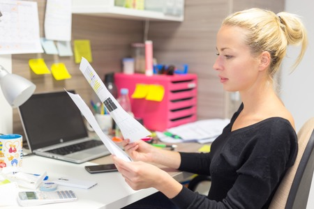Business and entrepreneurship consept. Beautiful blonde business woman working in colorful modern creative working environment reviewing some papers.