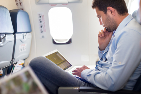 Foto de Casually dressed middle aged man working on laptop in aircraft cabin during his business travel. Shallow depth of field photo with focus on businessman eye. - Imagen libre de derechos