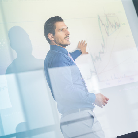 Photo pour Business man making a presentation in front of whiteboard. Business executive delivering a presentation to his colleagues during meeting or in-house business training. View through glass. - image libre de droit