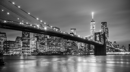 Photo pour Brooklyn bridge and New York City Manhattan downtown skyline at dusk with skyscrapers illuminated over East River panorama. Copy space. Black and white image. - image libre de droit