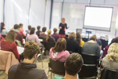 Photo pour Speaker giving presentation in lecture hall at university. Participants listening to lecture and making notes.  Trough the glass rear view of audience in lecture room. - image libre de droit