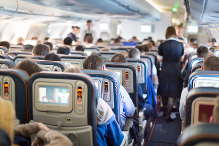 Photo pour Interior of large passengers airplane with people on seats and stewardess in uniform walking the aisle. - image libre de droit