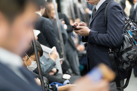 Interior of moder Tokyo metro with passengers on seats and businessmen using their cell phones. Corporate business people commuting to work by public transport. Horizontal composition.